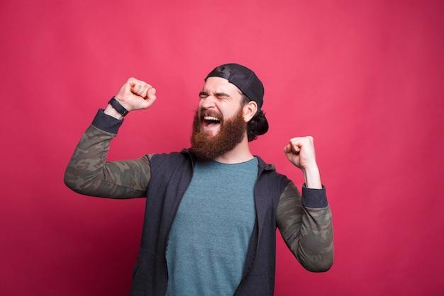 Фото веселый бородатый человек празднует победу.