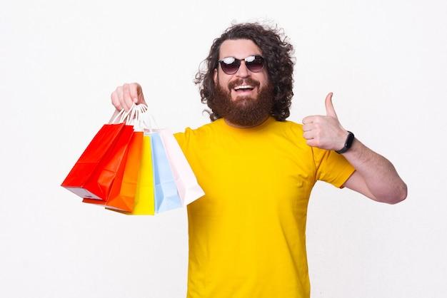 엄지 손가락을 표시하고 다채로운 쇼핑백을 들고 노란색 티셔츠에 쾌활한 수염 난 남자의 사진