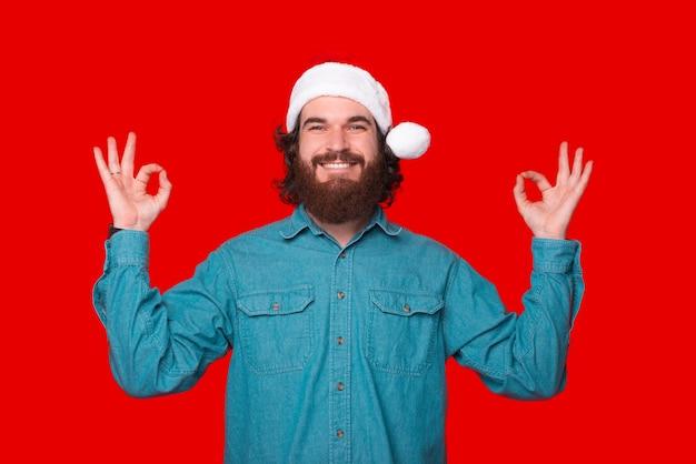Фото веселого бородатого мужчины в шляпе санта-клауса и делающего мир жестом дзен