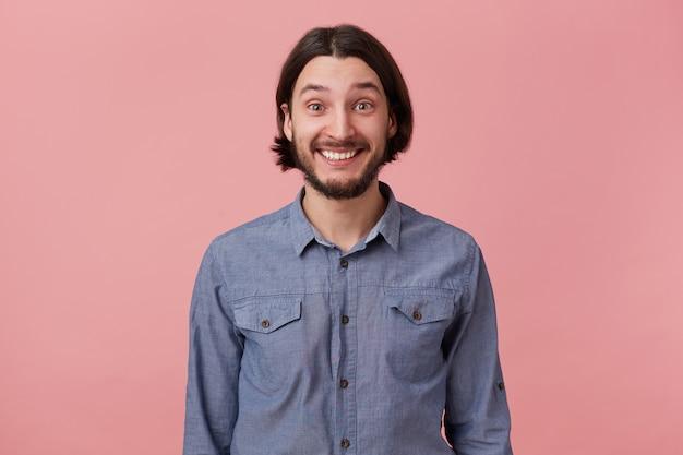 良い気分で長い櫛の黒髪の陽気なひげを生やした若い男の写真は、良いニュースを聞いて、ピンクの背景の上に孤立して、心から喜んで微笑んでいます。
