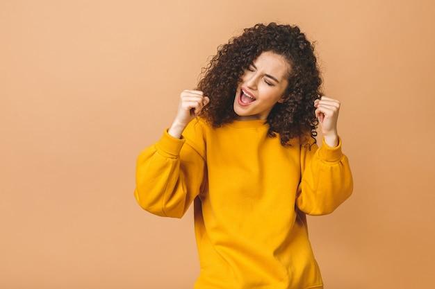 베이지 색 벽 배경 위에 절연 명랑 아름 다운 젊은 여자의 사진. 승자 제스처를 표시합니다. 행복 우승자 â'âââ elebrating 승리.