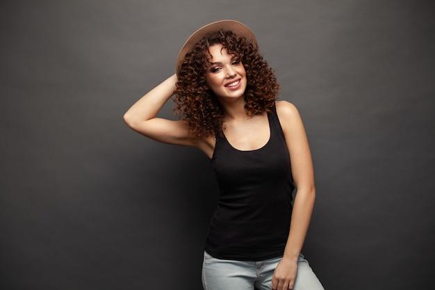 회색 벽에 고립 된 서 쾌활 한 아름 다운 젊은 여자의 사진