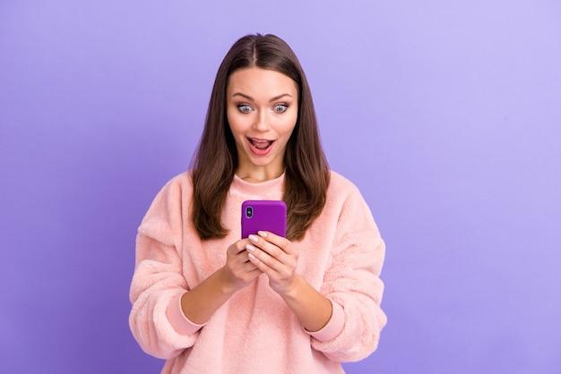 보라색 벽에 전화 오픈 입을 들고 쾌활한 블로거 아가씨의 사진