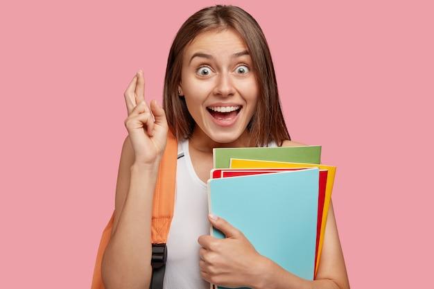 大喜びの表情で陽気なブルネットの女性の写真は指を交差させ続けます