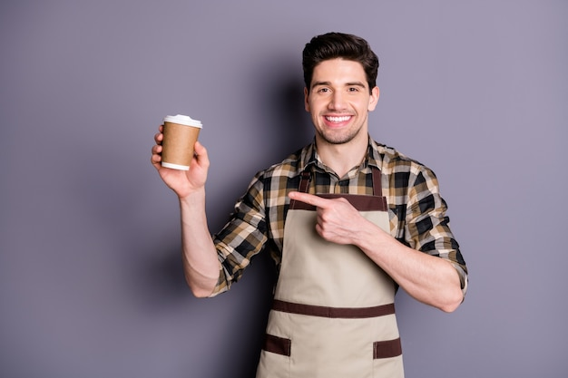 이 종류의 고립 된 회색 벽을 추천하는 일회용 커피 한잔을 가리키는 쾌활한 자신감 매력적인 잘 생긴 남자의 사진