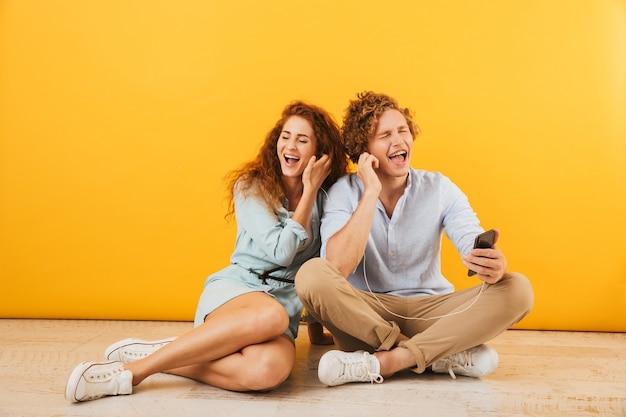 黄色の背景で隔離、一緒に床に座ってイヤホンで音楽を聴いている陽気なカップルハンサムな男性と巻き毛の女性の写真