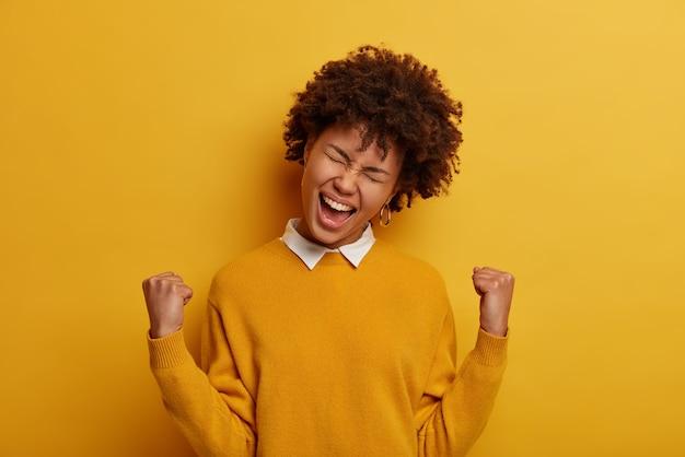 쾌활한 곱슬 머리 여자의 사진은 승자처럼 느껴지고, 주먹을 쥐고, 승리 제스처를 만들고, 행복으로 외치고, 노란색 점퍼를 착용하고, 목표를 달성하고, 승리를 얻고, 실내 포즈를 취합니다. 네, 해냈습니다!