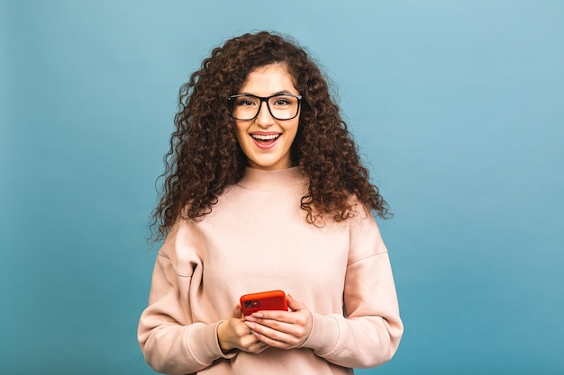 Фото веселой милой красивой молодой женщины, болтающей по мобильному телефону, изолированной на синем фоне стены.