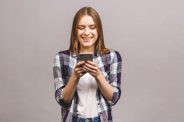 Фото жизнерадостной милой красивой молодой женщины беседуя мобильным телефоном изолированным над серой стеной стены.