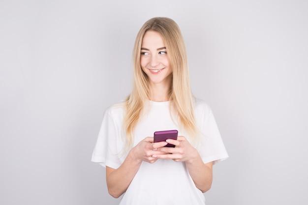 Фото веселой милой красивой молодой женщины в чате по мобильному телефону
