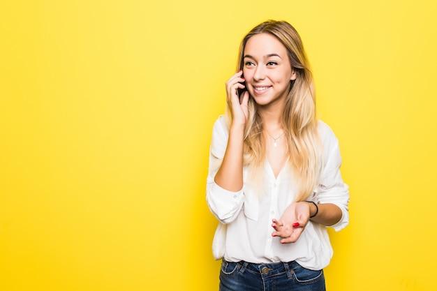 쾌활 한 귀여운 아름 다운 젊은 여자의 사진 노란색 벽 벽에 고립 된 휴대 전화에 대 한 얘기.