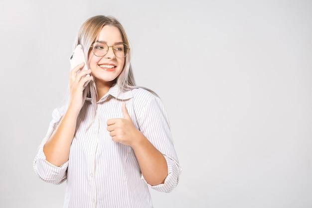 白い壁の背景に分離された携帯電話でチャットする陽気なかわいいビジネス美しい若い女性の写真。いいぞ。