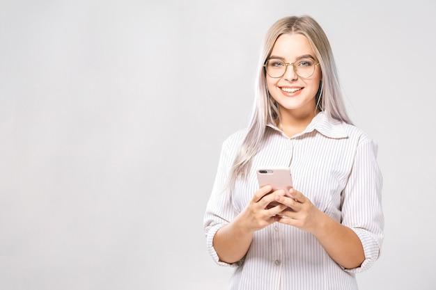 Фотография веселой милой деловой красивой молодой женщины в чате по мобильному телефону, изолированному на белом фоне стены.