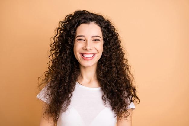 밝은 귀여운 매력적인 좋은 여자 친구의 사진은 베이지 색 파스텔 컬러 배경 위에 절연 카메라에 이빨 전송 미소