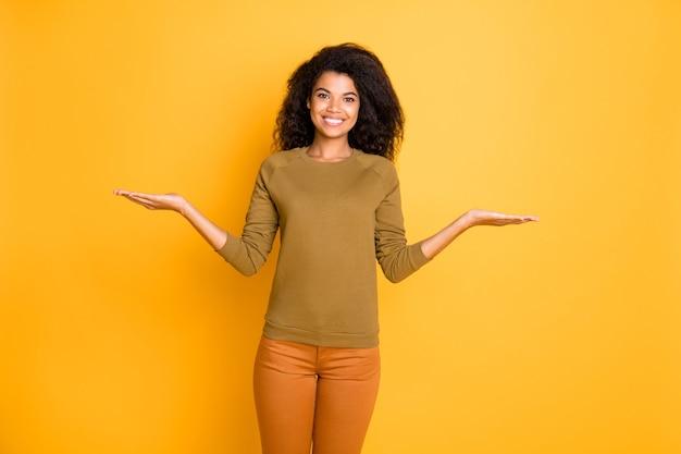 あなたが比較し、鮮やかな色の背景の上に分離されたズボンを着用して選択するための2つのオブジェクトを保持している陽気なかわいい素敵な魅力的な魅力的なガールフレンドの写真