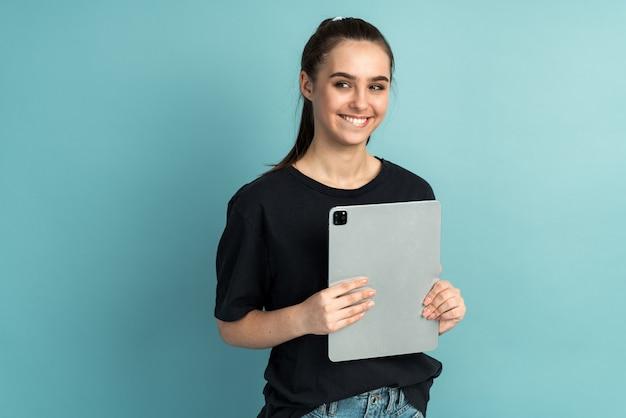 タブレットを持っている陽気なかわいい素敵な魅力的な女の子の写真