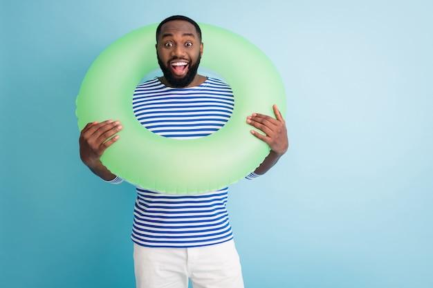 陽気な暗い肌の男の写真は首の周りに緑の救命浮環を保持します準備ができて泳ぐ海の海の旅行者良い気分晴れた日着用ストライプセーラーシャツ孤立した青い色の壁