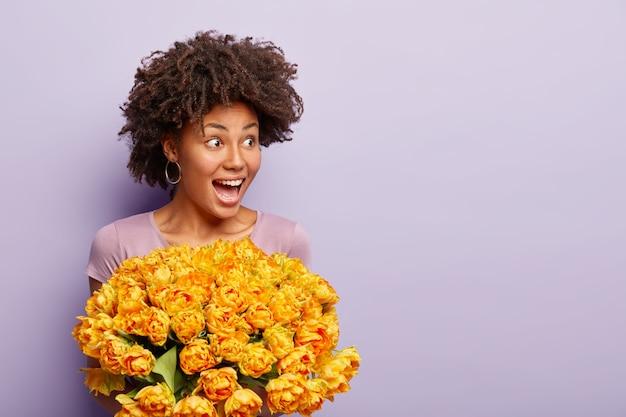 さわやかな髪の陽気な暗い肌の女性の写真、オレンジ色のチューリップを保持し、カジュアルなtシャツを着て、幸せを表現し、紫色の壁にポーズをとって、広告のための空きスペース。ガールフレンドは花を取得します