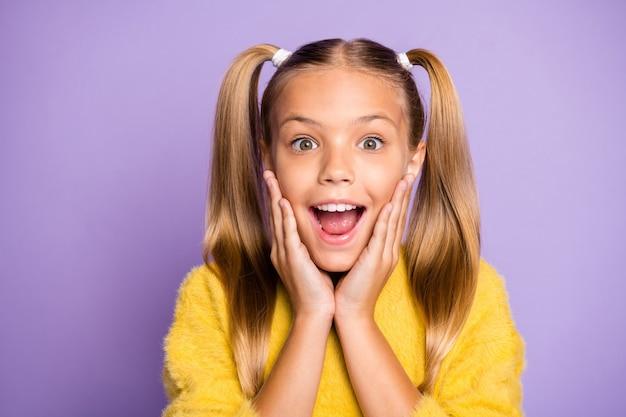 판매가 노란색 스웨터 고립 된 파스텔 바이올렛 컬러 벽을 입고 얼굴에 놀라움을 표현하기 시작했다는 것을 믿을 수없는 쾌활한 황홀한 기뻐서 소녀의 사진