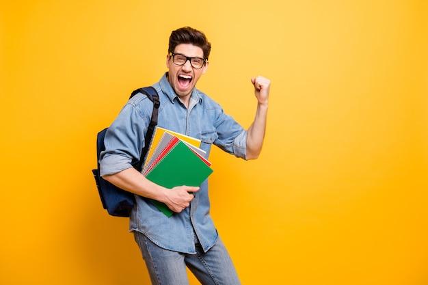 感情を表現する背後にあるランドセルで試験に合格すると叫んでいる陽気な興奮した狂った男の写真孤立した鮮やかな色の壁