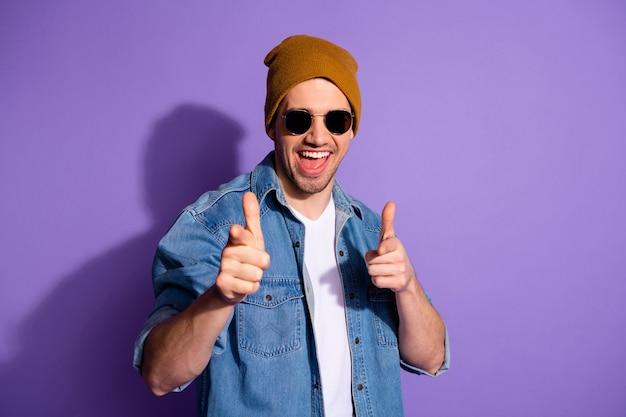 紫の鮮やかな色の背景の上に分離されたキャップの帽子を身に着けているあなたが選ばれることを望んでいるあなたを指している陽気な興奮したハンサムな男の写真