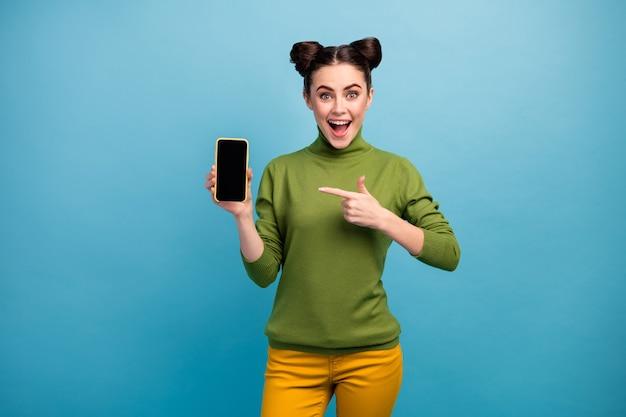 쾌활한 흥분된 여자의 사진 개최 새 모델 스마트 폰 선물 좋은 품질의 터치 스크린 장치 오픈 입 착용 녹색 터틀넥 노란색 바지 절연 파란색 벽