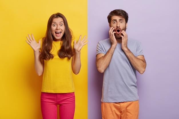 На фото веселая возбужденная женщина поднимает руки и что-то эмоционально восклицает, потрясенный мужчина смотрит с большим удивлением.