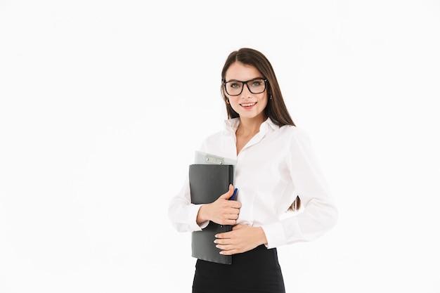 白い壁に隔離されたオフィスで働いている間、ドキュメントと本のバインダーを保持しているフォーマルな服を着た陽気な女性労働者の実業家の写真