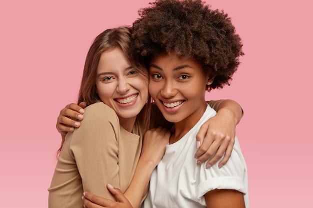 쾌활한 친근한 인종 간 여성의 사진은 따뜻한 포옹, 기꺼이 미소, 캐주얼 옷을 입은 가족 초상화 포즈, 분홍색 벽 위에 절연되어 있습니다. 우정