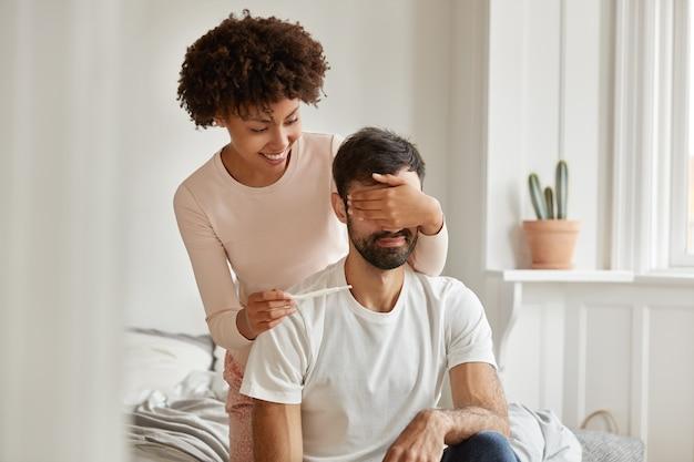 쾌활한 기쁜 어두운 피부의 젊은 여성의 사진은 남편의 눈을 가리고 예기치 않은 놀라움을 원하며 긍정적 인 임신 결과를 보여주고 침대에서 포즈를 취하고 부모가 될 것입니다. 출산 개념