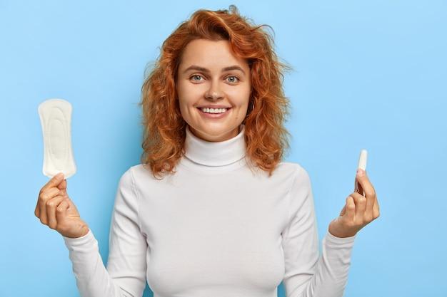 На фото жизнерадостная симпатичная женщина держит средства защиты во время менструации, держит ватную гигиеническую салфетку и тампон, контролирует менструальный цикл, носит белый джемпер. личная гигиена