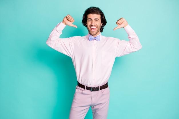 Фото веселого хорошего настроения, волнистые волосы, мужчина в розовом наряде, указывая на себя двумя большими пальцами, изолировал фон бирюзового цвета