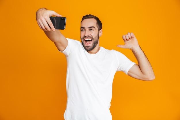 Фотография жизнерадостного парня 30-х годов в повседневной одежде, кричащего и делающего селфи на мобильном телефоне, изолирована
