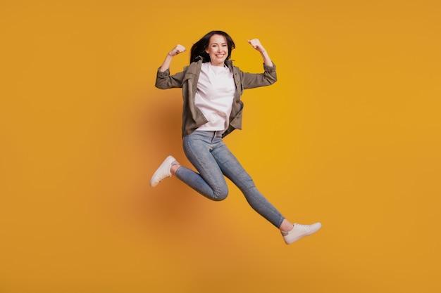 Фото жизнерадостной дамы поднимают бицепс, прыжок руки изолированы на желтом фоне