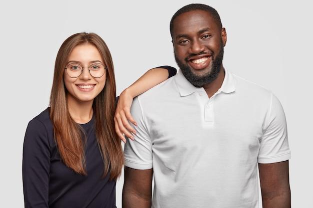 Фото веселой милой разноплановой пары улыбаются позитивно, стоят рядом друг с другом