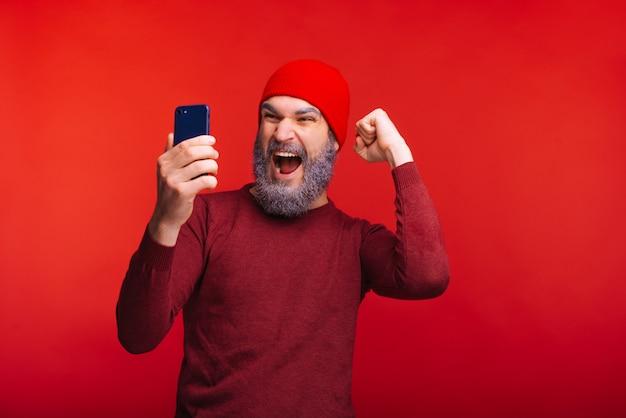 Фото веселый человек с белой бородой и красной шапочкой, глядя на смартфон и празднование успеха