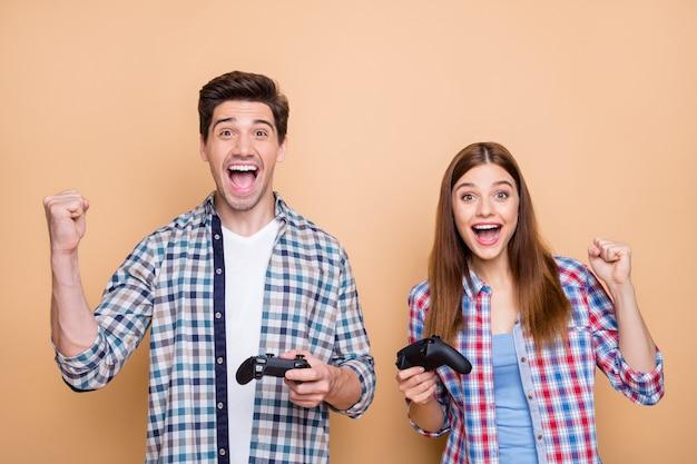 Фотография веселой позитивной случайной белой шатеной пары, играющей в видеоигры для playstation, радующейся победе, держащей джойстики руками, изолированными на бежевом пастельном цветном фоне