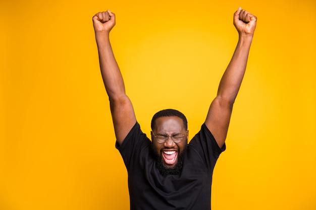 Фотография веселого позитивного сумасшедшего возбужденного мужчины в очках, черная футболка, кричащего, кричащего с грубым выражением лица, мечтающего поднимать руки вверх, изолированная яркая цветная стена