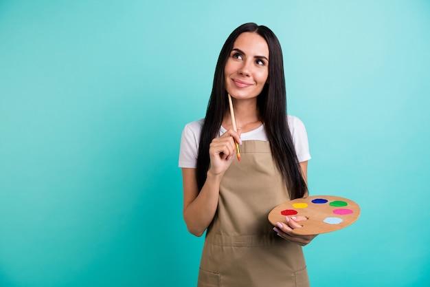 Фотография веселой позитивной милой красивой женщины, которая смотрит вверх в порыве мыслей, фантазирует, что рисовать, держа кисть красочной палитрой, изолированной бирюзового цвета, яркий фон