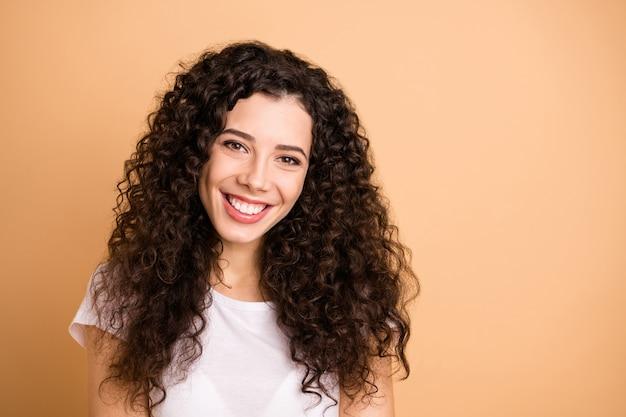 Фото веселой позитивной милой великолепной подруги, зубасто улыбающейся, нежно изолированной на бежевом пастельном цветном фоне