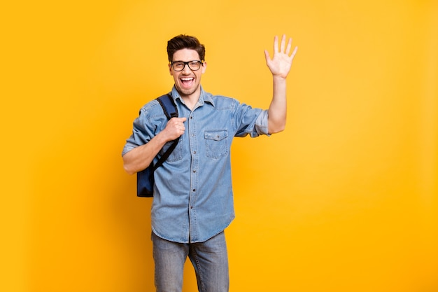 あなたに手を振っている陽気な前向きなかわいい男の写真は、あなたが孤立した鮮やかな色の壁を見てうれしい笑顔を浮かべています