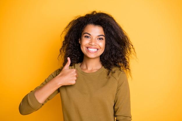 Фотография жизнерадостной, позитивной, милой, очаровательной, симпатичной чернокожей подруги показывает вам большой палец вверх, демонстрирует хорошее качество и зубы, изолированные на ярком цветном фоне