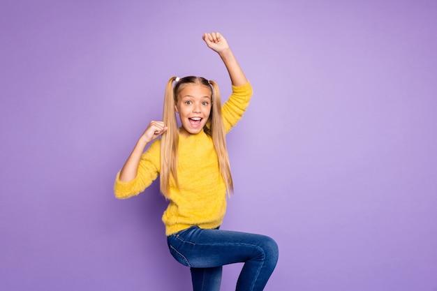 孤立したパステルカラーの紫色の壁を叫んでいる顔に驚きと黄色のセータージーンズデニムを着ている陽気なポジティブ興奮した女の子の写真