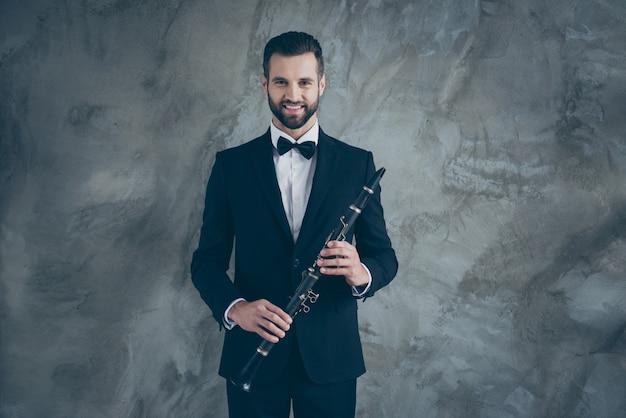 Фото веселого позитивного веселья профессионального музыканта в костюме, держащего кларнет перед игрой, зубасто улыбающегося изолированного серого цвета бетонной стены стены