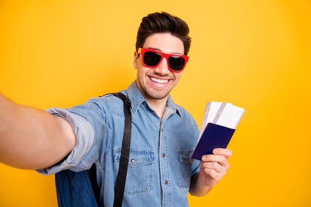 Фотография веселого позитивного красивого привлекательного мужчины, улыбающегося зубастой в красных солнцезащитных очках, изолировала себя, делающего селфи над яркой цветной стеной