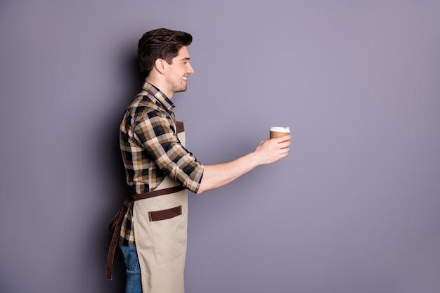 쾌활한 긍정적 인 잘 생긴 남자 미소 이빨 빛나는 사진은 카페 방문자 격리 된 회색 벽에 커피를주는 바리 스타로 일하고 손을 스트레칭