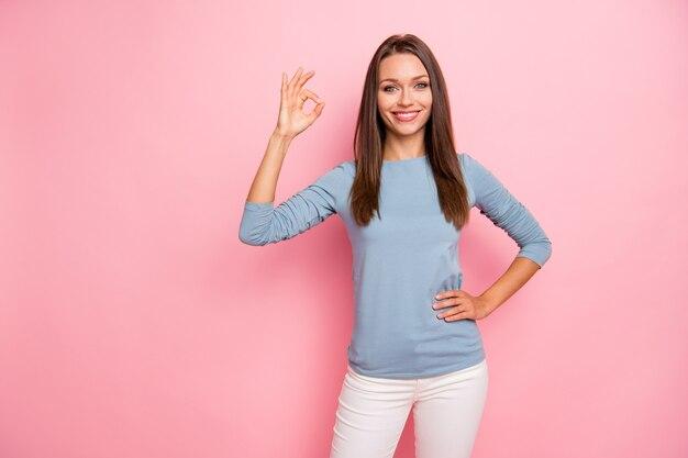Фото веселой позитивной довольно милой милой милой девушки, показывающей вам знак ок, держащую руку на талии, изолированный пастельный цвет фона
