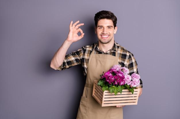 Фотография веселого позитивного зубастого сияющего человека, улыбающегося зубасто, показывая знак ок, держащего коробку с цветами рукой, изолировал стену серого цвета