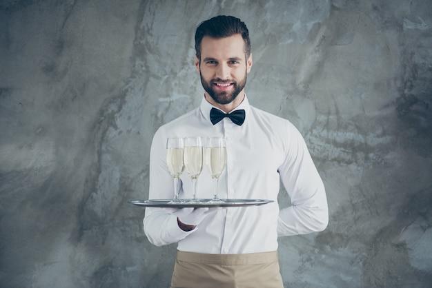 Фотография веселого позитивного зубастого сияющего официанта, держащего поднос с бокалами игристого напитка, изолированного над серой бетонной стеной