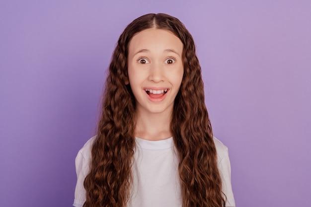 陽気なプレティーンの女の子の写真は紫色の背景に分離されたニュースを驚かせた